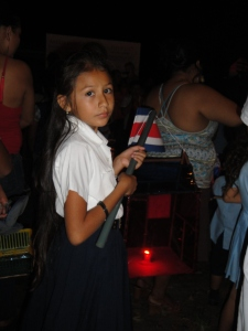 A Costa Rican girl lights a candle inside a house with her country's flag.
