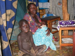 A woman with her kids in hut at Anaka IDP camp. Rosebell Kagumire photo.