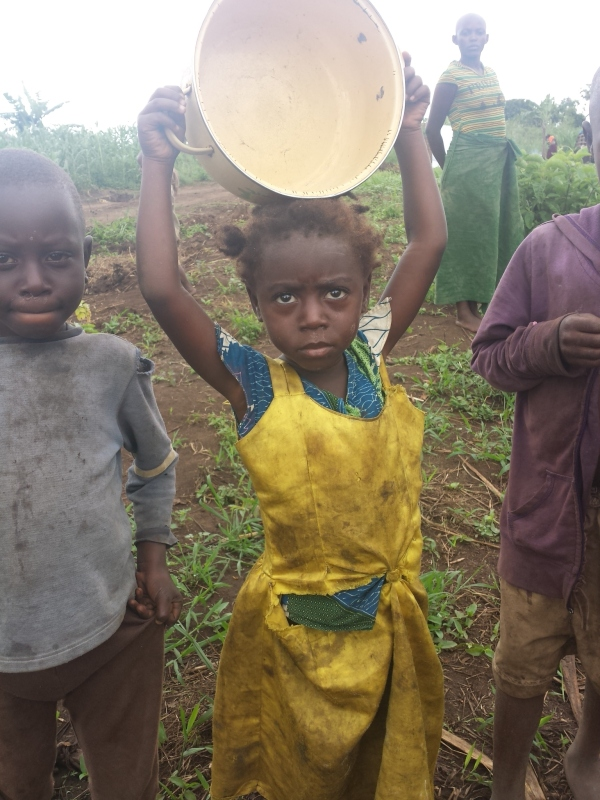 A young Congolese refugge girl carries an empty pan. Food for children is difficult to get for newly arrived refugees. Mostly they get maize flour and posho. Mostly children meals are given to very young ones.